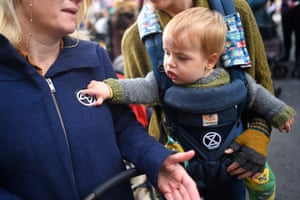 A toddler in a front-facing baby carrier with an Extinction Rebellion logo