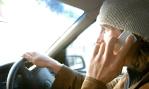 Man driving while using mobile phone