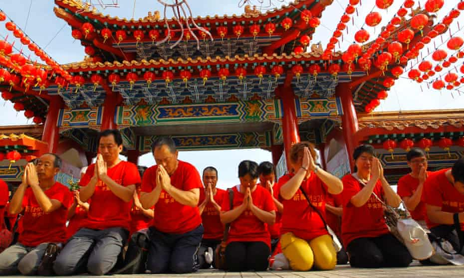 Relatives of Chinese passengers from the missing Malaysia Airlines flight MH370 attend prayers in Thean Hou temple, Kuala Lumpur, as the anniversary of the plane's disappearance approaches.