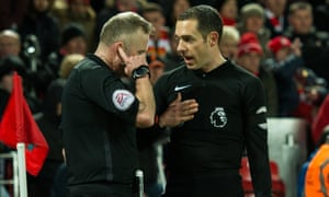 Jon Moss (left) talks with his assistant Eddie Smart and with the fourth official via his earpiece before awarding a penalty to Tottenham.