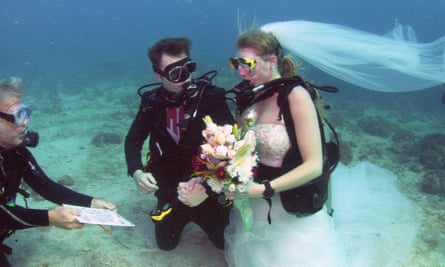 A notary public shows wedding vows written on an underwater tablet to Mould and Hyde during their underwater wedding ceremony Thursday.