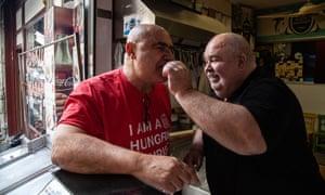 Ahmet Yazgüneş feeds David Califa at his fish shop.
