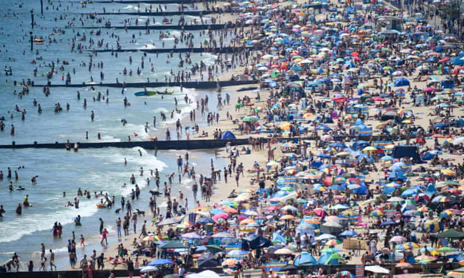 Thousands of  visitors crowd together on Bournemouth beach on June 25.