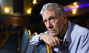 amos oz seated and leaning his chin and forearm on the back of a chair