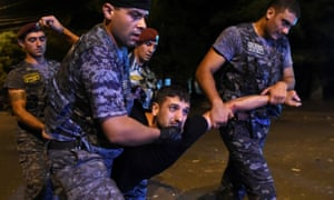 Police officers detain a protesters during demonstration in Yerevan