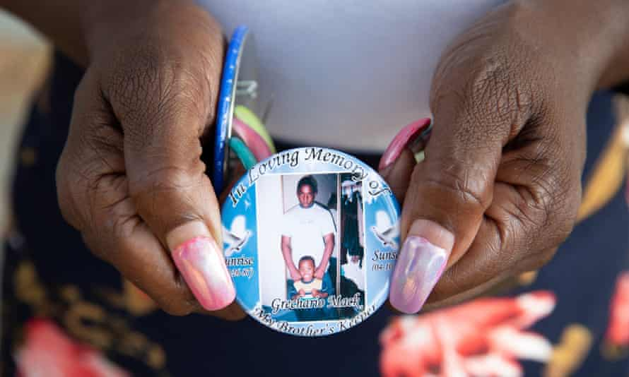 Catherine Walker, mother of Grechario Mack, holds a badge in Los Angeles last year.
