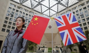 An employee stands next to the Chinese and British flags