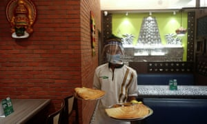 A waiter wearing a protective mask and face shield carries food on trays at a newly reopened restaurant in Mumbai on Monday.