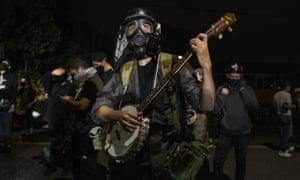 A protester plays a banjo during the nightly protests at a Portland police precinct