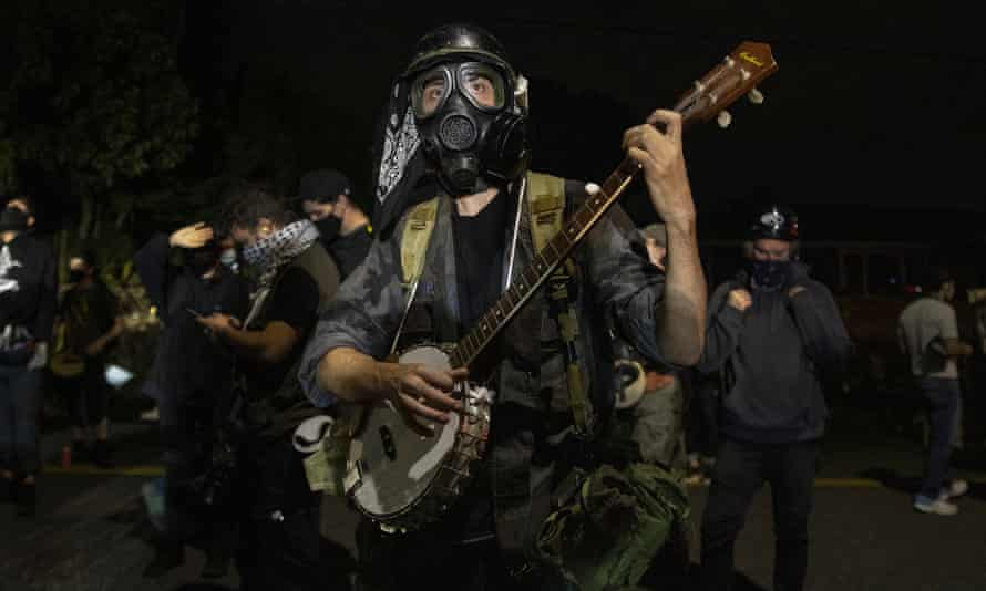 A protester plays a banjo during the nightly protests at a Portland police precinct on Sunday. The protest was declared an 'unlawful gathering' by Portland police.