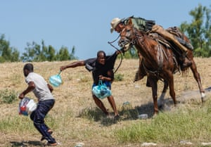 Texas, USA mounted United States Border Patrol agent attempts to stop a Haitian migrant from entering an encampment on the banks of the Rio Grande near the Acuna Del Rio International Bridge.