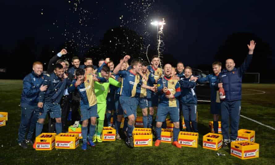 East Kilbride players and staff celebrate with beer presented by Ajax club officials.