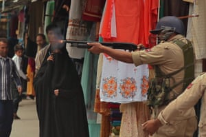 A police officer fires pellets to disperse protesters in Srinagar, India