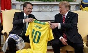 Brazilian president Jair Bolsonaro presents Donald Trump with a national team soccer jersey at the White House, March 2019.