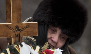 The mother of Elena Volkova, a victim of recent shelling, cries at her daughter's grave during her funeral in Avdiivka.