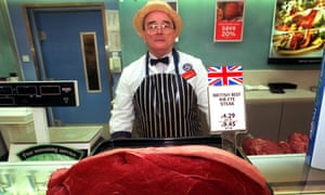 A butcher standing behind a piece of British beef at the meat counter of Sainsbury's.