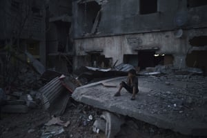 A boy closes his eyes as he plays hide-and-seek at dusk in a neighbourhood heavily damaged by airstrikes during an 11-day war between Gaza's Hamas rulers and Israel.