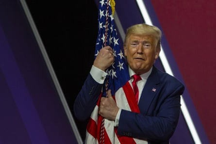 Donald Trump hugs the flag at CPAC on Saturday. 'America vs socialism' was the official theme of this year's CPAC, a slogan stamped all over the convention centre.