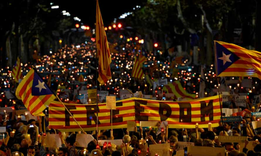"Crowds hold a giant Estelada (pro-independence Catalan flag) reading ""Freedom"" during candle-lit demonstration in Barcelona against the arrest of two Catalan separatist leaders this week"