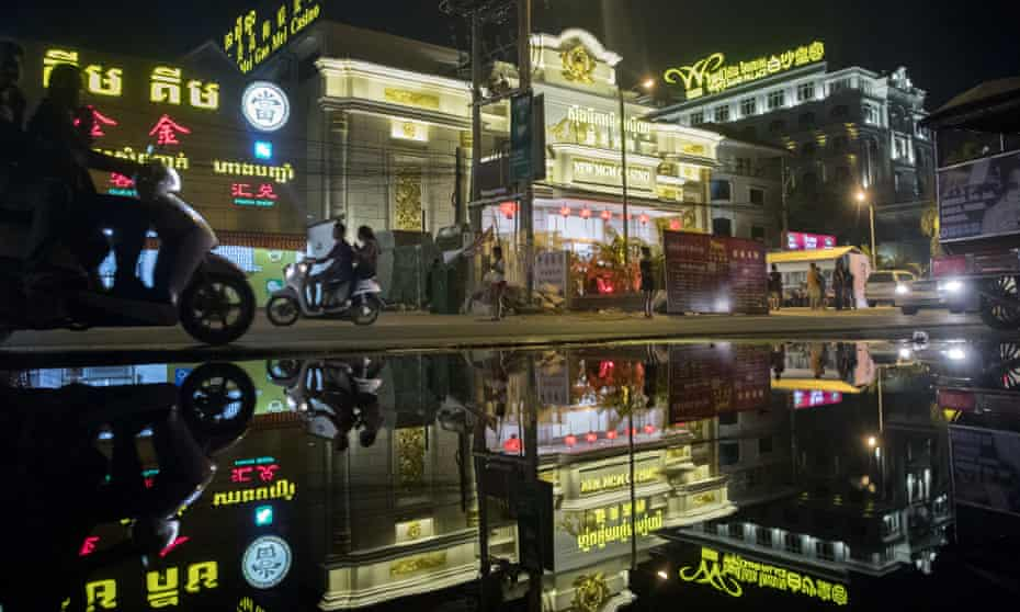 Motorcyclists and the New Mei Gao Mei (New MGM) casino are reflected in a puddle at night in Sihanoukville, Cambodia