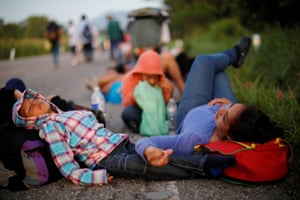 Glenda Escobar, 33, a migrant from Honduras, part of a caravan of thousands from Central America en route to the United States, takes a rest on the road with her children Adonai and Denzel, on their way to Pijijiapan from Mapastepec, Mexico