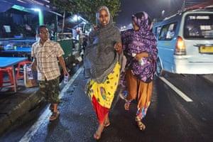 Somalian refugees Norta and Khadro walking in a Jakarta street at night.