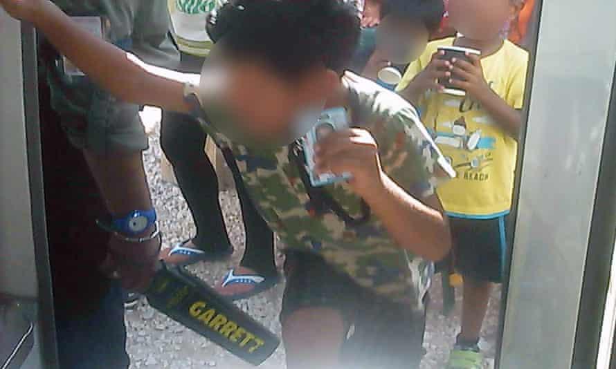 A young asylum seeker boy on Nauru holds up his ID card as a guard wands him.