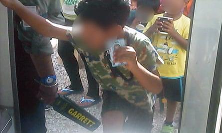 An asylum seeker boy on Nauru holds up his ID card as a guard searches him
