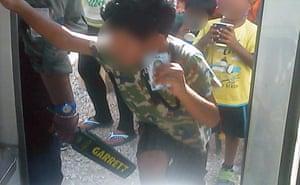 A young asylum seeker boy holds up his ID card on Nauru