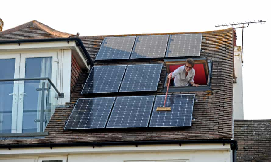 A woman cleaning the solar panels on her roof