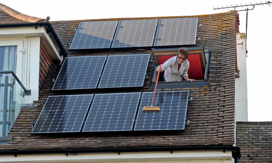 Woman cleaning dust of her solar panels with a broom
