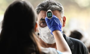 A man gets his temperature checked at a bus station amid the Covid-19 pandemic in Santiago, Chile, which has proposed issuing 'immunity passports' – a practice the WHO warned today could be dangerous.