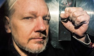 Julian Assange gesturing from a prison van in May.