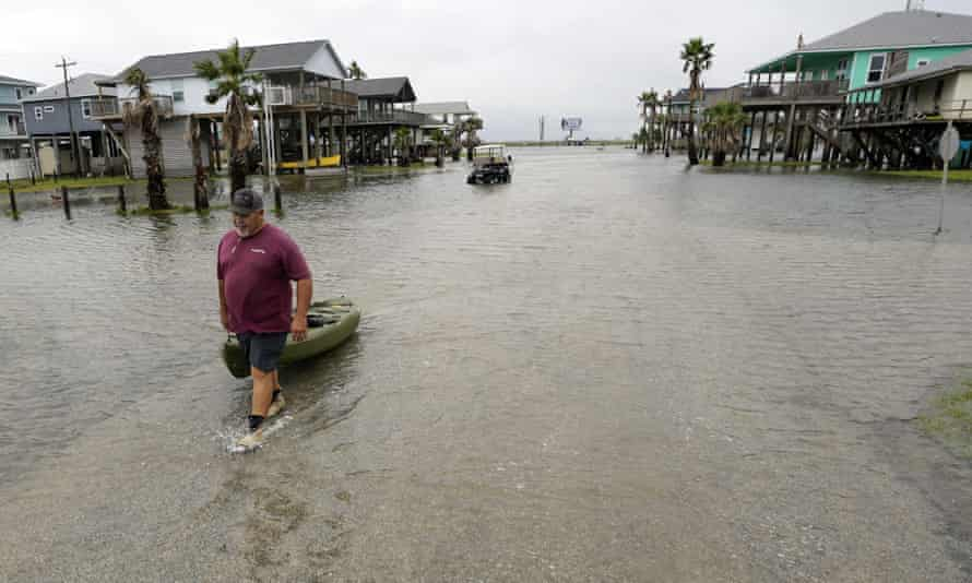 Bubba Ferguson drags a boat through a flooded street in the aftermath of Hurricane Nicholas on Tuesday in San Luis Pass, Texas.