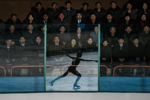 An ice skater reflected in a glass panel at the 26th Paektusan prize figure skating festival, in celebration of the day of the shining star, part of celebrations marking the birthday of late North Korean leader Kim Jong-il.