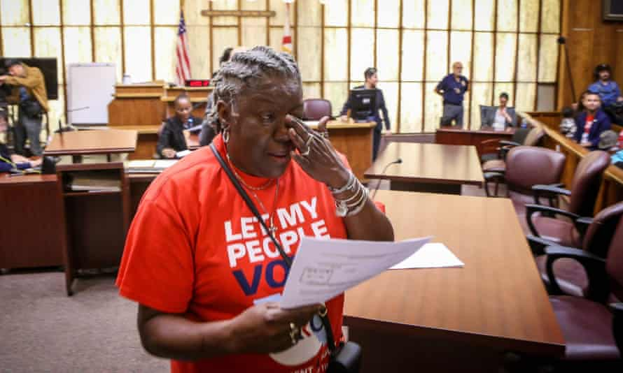 Carmen Brown weeps as she walks away holding a paper restoring her right to vote during a special court hearing aimed at restoring the right to vote last year in Miami.