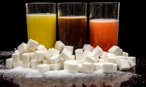 Pile of sugar cubes in front of trio of soft drinks
