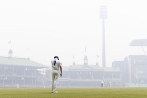 New South Wales' Liam Hatcher stands in the outfield as bushfire haze covers the pitch during the Sheffield Shield cricket match against Queensland.