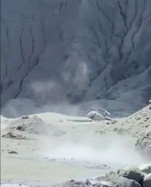 An image shows a helicopter on its side after the eruption on White Island.