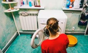 A woman loads washing machine.