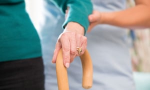 A carer helps a person with a walking stick