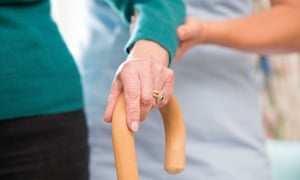 An elderly woman's hand on a walking stick with a care worker supporting her arm
