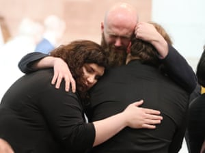 Mourners embrace ahead of the funeral