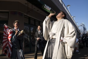 A man legally swigs sake from a bottle on his way to an after party