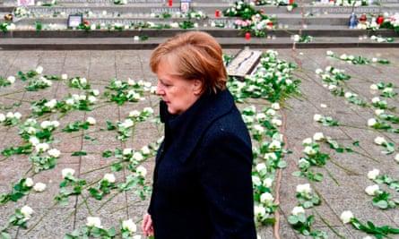 Angela Merkel walks past the memorial for victims of last year's truck attack at Breitscheidplatz Christmas market in Berlin.