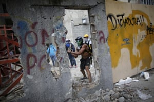 An anti-government demonstrator attacks a wall with a pickaxe to release pieces of concrete to throw at police during a protest against the installation of the  constituent assembly in Caracas.