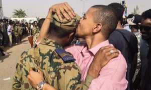 A Sudanese anti-regime protester kisses a soldier on the head.