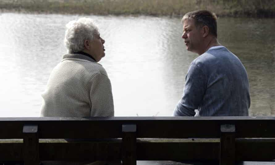 Elderly mother and son arguing on a park bench