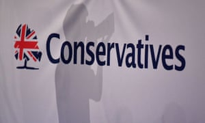 A photographer is seen against the background of a Conservative party banner