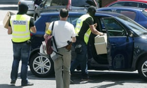 Police officers confiscate materials belonging to the athletics coach Jama Aden, who was arrested at the Arrahona hotel, in Sabadell, Spain on Monday.